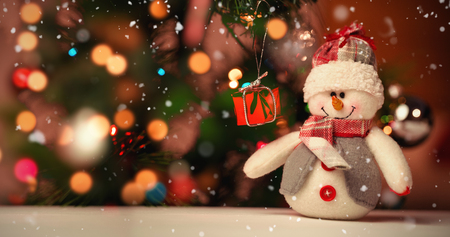 Snow falling against close up of snowman on wooden table