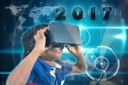 virtual reality simulator: Boy wearing virtual reality simulator  against abstract blue pattern Stock Photo
