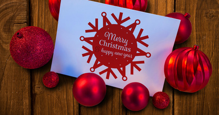 Red christmas baubles surrounding white page against bleached wooden planks background