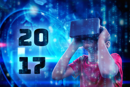 virtual reality simulator: Boy with virtual reality simulator against digitally generated black and blue matrix Stock Photo