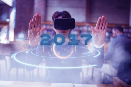 arm raised: Digital image of new year 2017 against woman using virtual reality simulator with arm raised Stock Photo