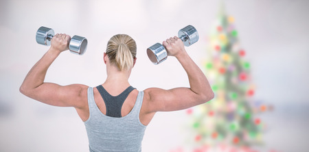 Muscular woman working out with dumbbells  against blurry christmas tree in room Muscular woman working out with dumbbells on white background Imagens