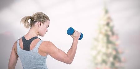 筋肉女ぼやけてクリスマス ツリー ホワイト バック グラウンドにダンベルでワークアウト ルーム筋肉女性に対してダンベルでワークアウト 写真素材