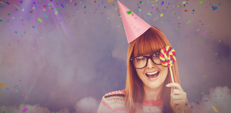 Smiling hipster woman with lollipop and hat party against illuminated disco lights at nightclub Stock Photo