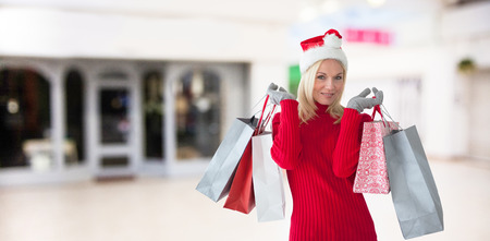 Happy festive blonde with shopping bags against interior of modern shopping mall Stock Photo