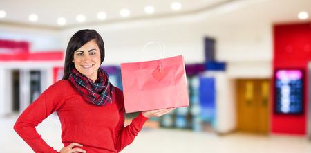 vestidos de epoca: Brunette sonriente que muestra bolsa de regalo de color rojo contra la imagen borrosa de tienda Foto de archivo