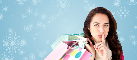 Woman wearing a scarf and holding shopping bags against snowflakes against blue background photo