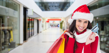 Excited brunette holding shopping bags and credit card  against interior of modern shopping mall