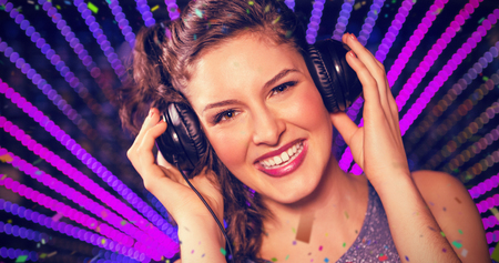 Pretty female DJ playing music against flying colours Stock Photo