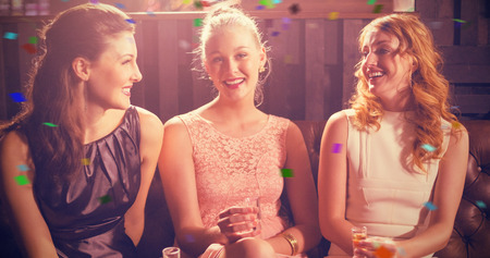 shot glass: Three female friends holding shot glass of tequila in bar against flying colours