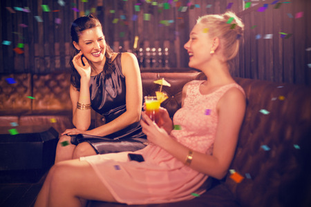 Female friends interacting with each other while having cocktail against flying colours Stock Photo