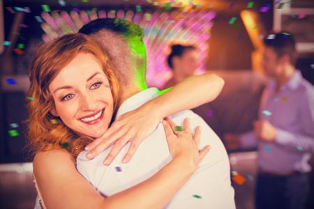 socializando: Sonriente pareja abrazándose en la barra contra los colores de vuelo