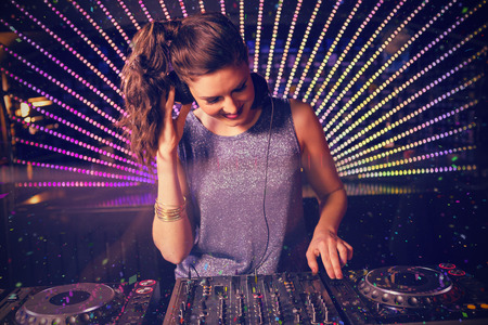Pretty female DJ playing music against flying colours Stock Photo - 66815378