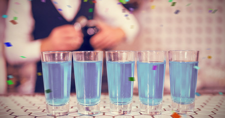 blue lagoon: Glasses of blue lagoon drinks on bar counter against flying colours Archivio Fotografico