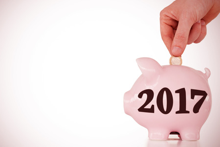 financial year: Hand inserting a coin in a pink piggy bank against digital image of new year 2017
