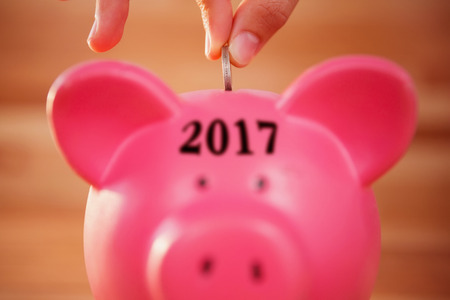 financial year: Digital image of new year 2017 against close-up of hand inserting coin in piggy bank