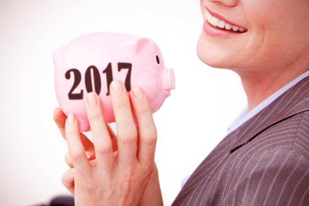 profit celebration: Cheerful businesswoman holding a piggybank  against digital image of new year 2017