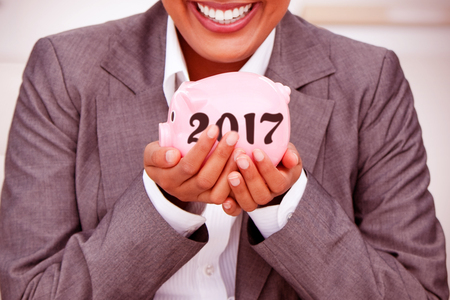 charismatic: Close up of a smiling businesswoman holding a piggybank  against digital image of new year 2017