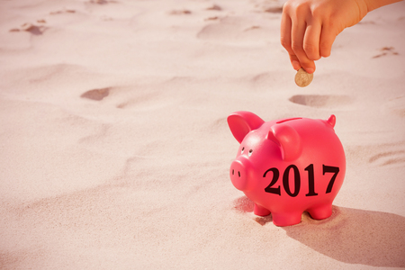 profit celebration: Digital image of new year 2017 against hand putting a coin in the piggy bank Stock Photo