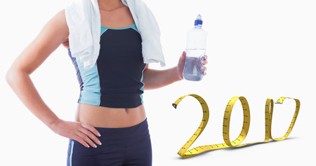 midsection: 3D Midsection of sporty woman with towel around neck and water bottle against 2017 made of measuring tape Stock Photo