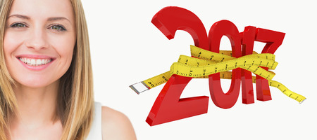 tape measure: 3D Portrait of cute young woman smiling against digitally generated image of new year with tape measure Stock Photo