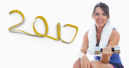 3D Portrait of woman sitting and exercising with dumbbell against 2017 made of measuring tape