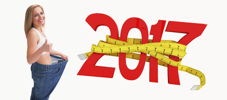 3D Portrait of woman wearing old pants after losing weight and gesturing thumbs up against digitally generated image of new year with tape measure