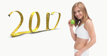 3D Portrait of happy young woman holding green apple against 2017 made of measuring tape