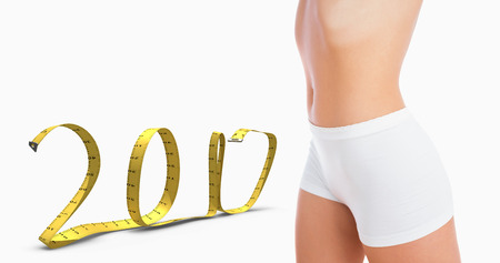 midsection: 3D Midsection of female slender body in shorts against 2017 made of measuring tape Stock Photo