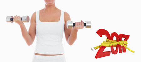 women working out: 3D Midsection of woman exercising with dumbbells against digitally generated image of new year with tape measure Stock Photo