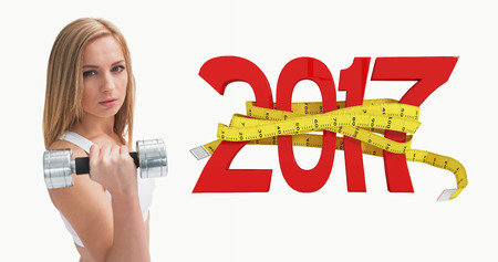 3D Portrait of young woman exercising with dumbbell against new year with tape measure