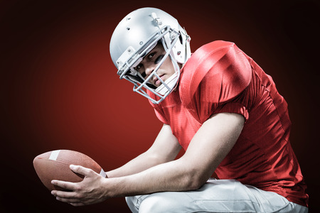 padding: Portrait of American football player crouching while holding ball against red background with vignette