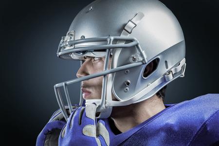 Sportsman wearing helmet looking away against blue background with vignette Stock Photo