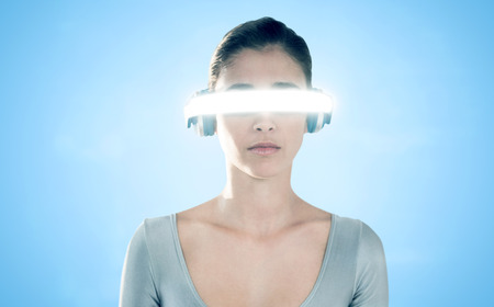 3D Young woman using virtual video glasses against blue background Stock Photo