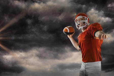 3D American football player throwing football against gloomy sky Stock Photo