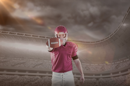 3D Portrait of american football player showing football to camera against mountain during tornado disaster