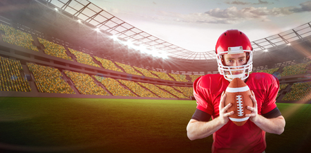 3D Portrait of focused american football player holding football against red background with vignette