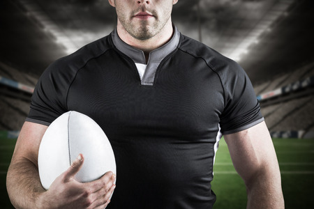 3D Tough rugby player holding ball against sport stadium at night Stock Photo