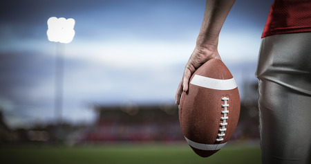 3D Cropped image of American football player holding ball against pitch
