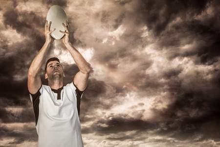 3D Rugby player holding rugby ball against gloomy sky