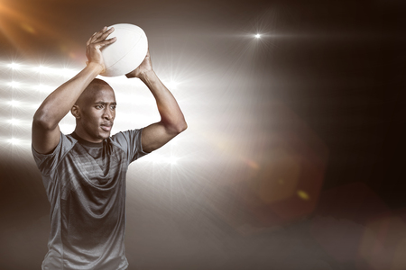 3D Confident sportsman throwing rugby ball against spotlight Stock Photo
