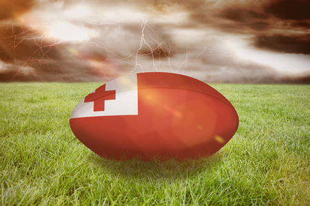 3D tonga rugby ball against stormy dark sky with lightning bolts