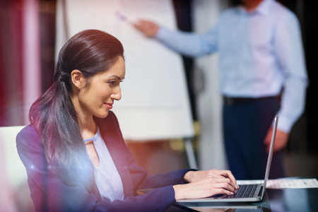 confident business woman: Portrait of businesswoman working on laptop in office