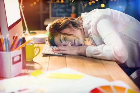 Tired businesswoman sleeping on desk in office Stock Photo