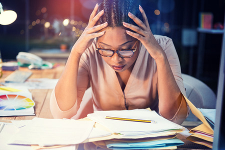 uneasy: Stressed businesswoman sitting at desk in office