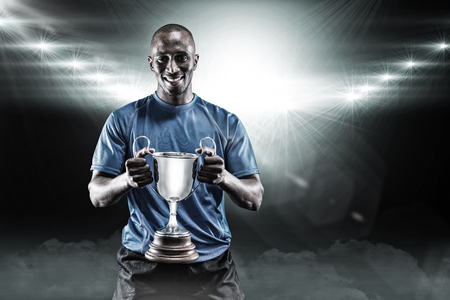 Portrait of happy athlete holding trophy against spotlight 3D
