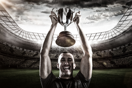silver screen: Portrait of successful rugby player holding trophy against rugby stadium 3D Stock Photo