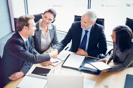 High angle view of businessmen shaking hands in conference room at office