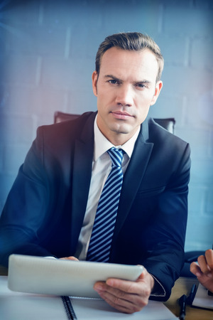 Portrait of businessman using digital tablet in conference room at office