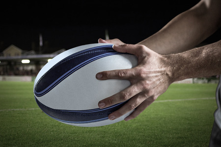 Cropped image of sports player holding ball against pitch and stands 3D